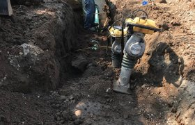 Crew member of Selly Excavating working in a trench to install a city drainage system