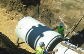 Excavator being used to lower a large section of concrete piping