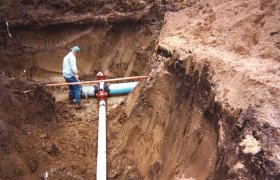 Crew member standing in a trench at the junction point of underground water pipes