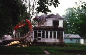 Selly Excavating using a large excavator to demolish a two story house
