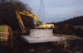 Lowering a large concrete culvert into a pit