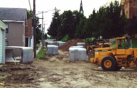 Concrete culverts sitting at a road construction site in a town