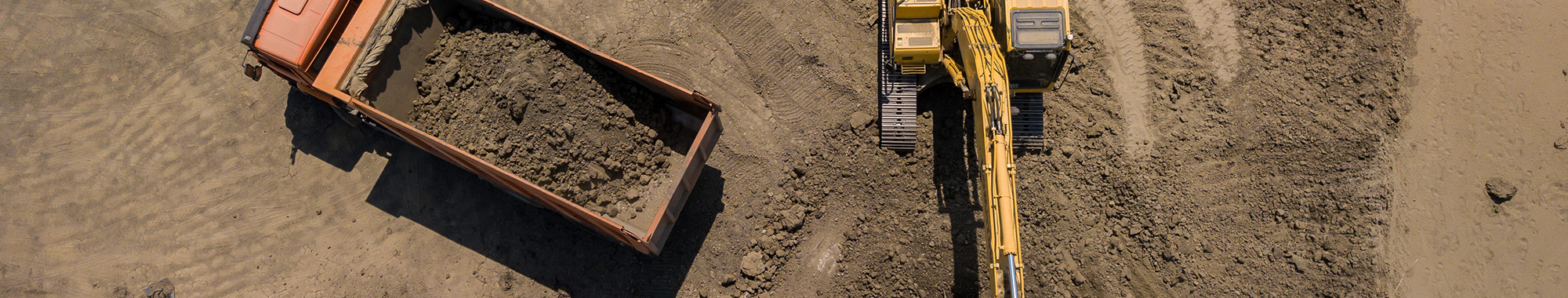 Aerial photo looking overhead at an excavator filling a dump truck